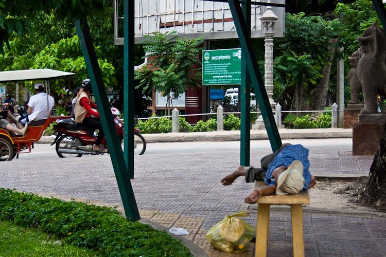 Мужчина отдыхает на лавочке в Сием Рипе