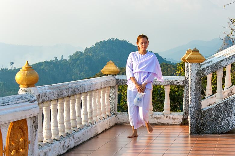 Молодая монахиня спускается по лестнице храма